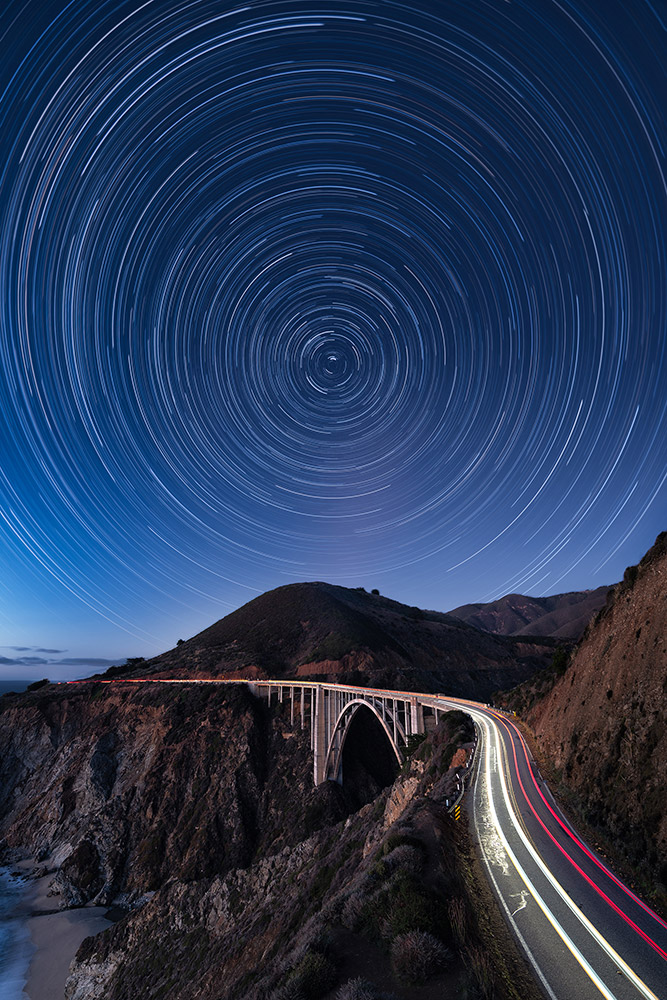 The night sky spinning around the North Star while cars drive through the Bixby Bridge on the Pacific Coast Highway in Central California (USA) by Marcin Zajac