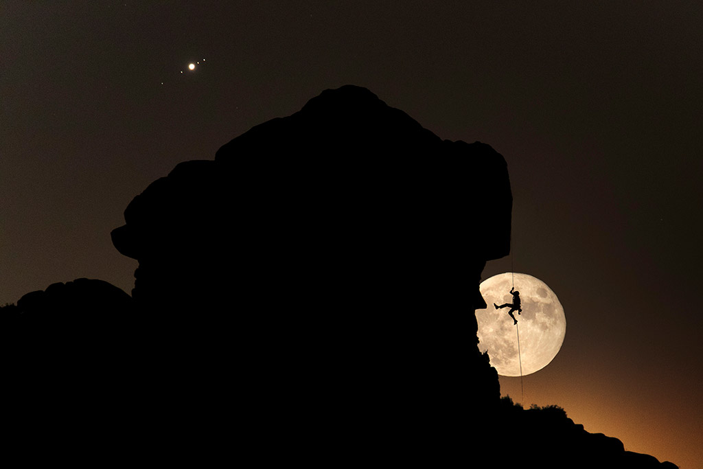 Full Moon and Jupiter with its moons over a climber silhouette in La Pedriza (Spain) by Dani Sanz