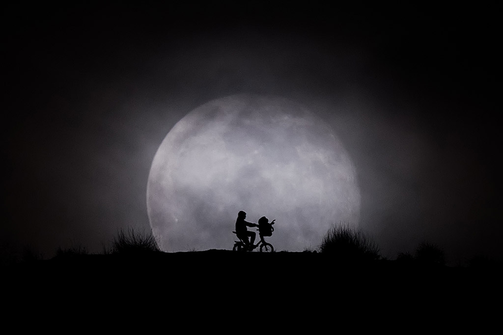 Elliott and E.T. silhouette behind a Full Moon (Madrid, Spain) by Kike Bustos